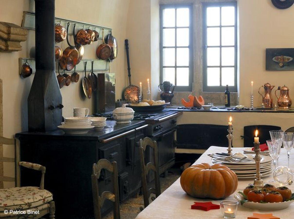 Une cuisine campagne qui expose ses casseroles à l'ancienne