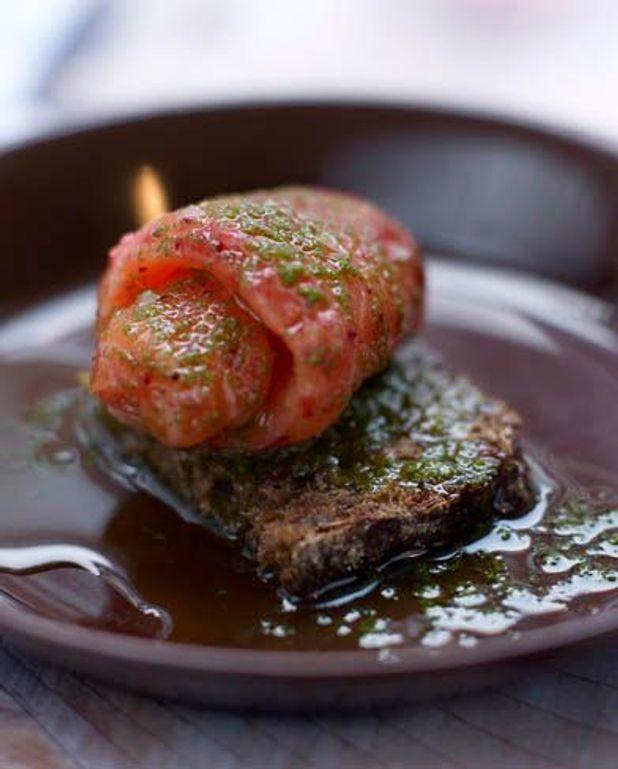 Saumon mariné aux airelles, servi avec estragon et huile à l'ail