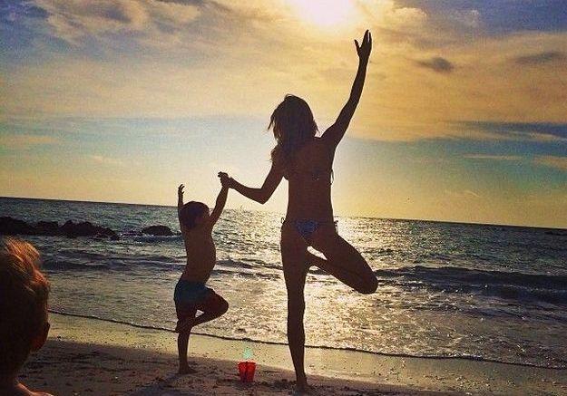 Petite posture de yoga en famille face au coucher de soleil