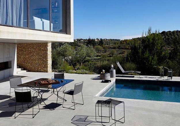Une terrasse avec piscine au mobilier monochrome