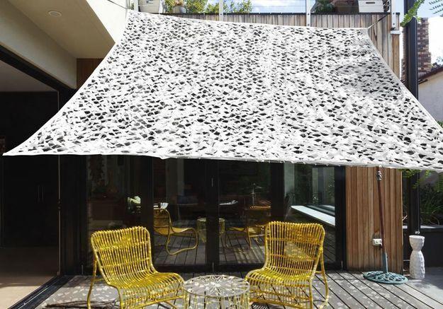 Une terrasse avec piscine qui propose un petit salon ombragé