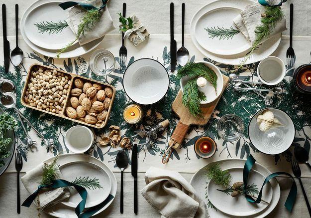 L'idée qu'on pique à la collection Noël H&M Home : réaliser une déco de table avec des branches de sapin entourées d'un ruban en satin vert