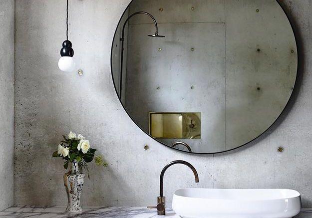 Le miroir rond dans une salle de bains minérale pour adoucir l'atmosphère