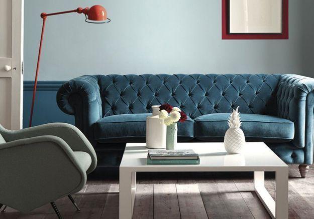Un canapé en velours bleu canard mêlé à du rouge