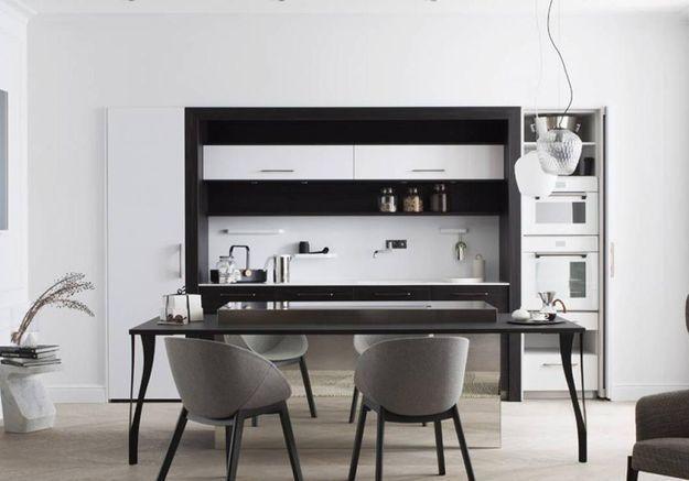 Cuisine noire et blanche qui se cache grâce à des portes coulissantes
