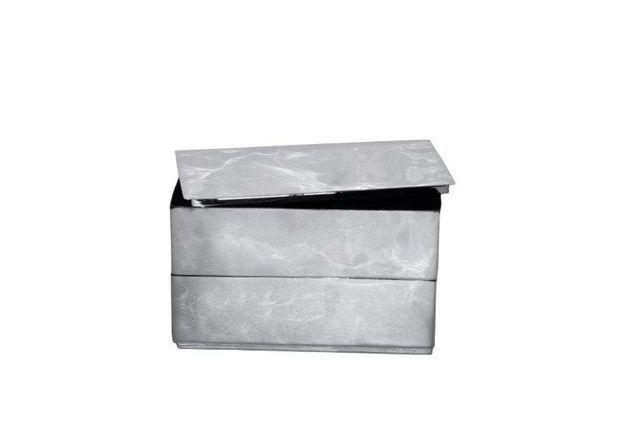Un canapé gris accompagné d'une boite métallique