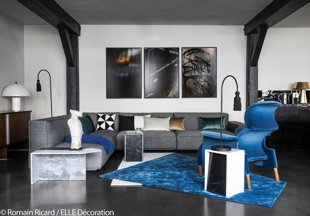 Salon noir et blanc éclairé par des touches bleu roi