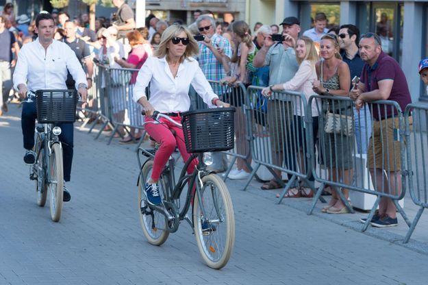 Brigitte Macron, en jean rose, chemise blanche et baskets pour une sortie vélo