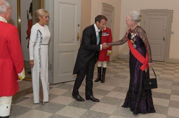 Brigitte Macron en robe longue blanche et bordures lamées