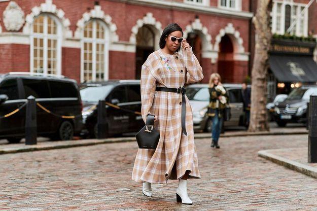 Un manteau long ceinturé pimenté d'une paire de bottines blanches