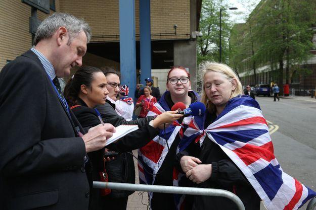 Les fans, équipés d'un drapeau de l'Angleterre pour se tenir chaud, répondent aux questions des journalistes
