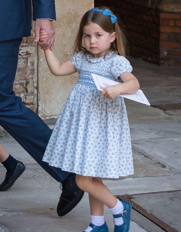 Charlotte arbore une raie au milieu et un serre-tête bleu pour le baptême de son petit frère Louis, le 09 juillet 2018.