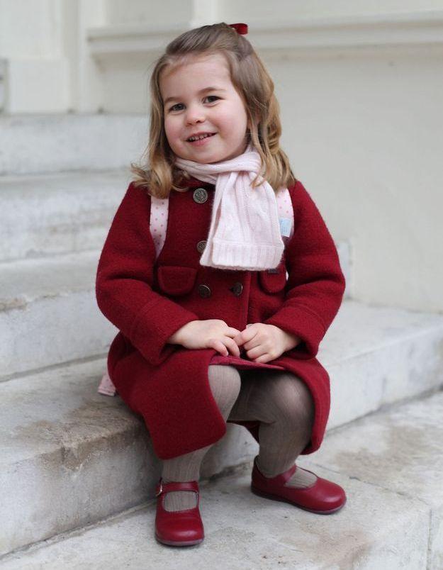 Charlotte pose pour sa première rentrée des classes. Ses cheveux sont noués dans un ruban rouge.