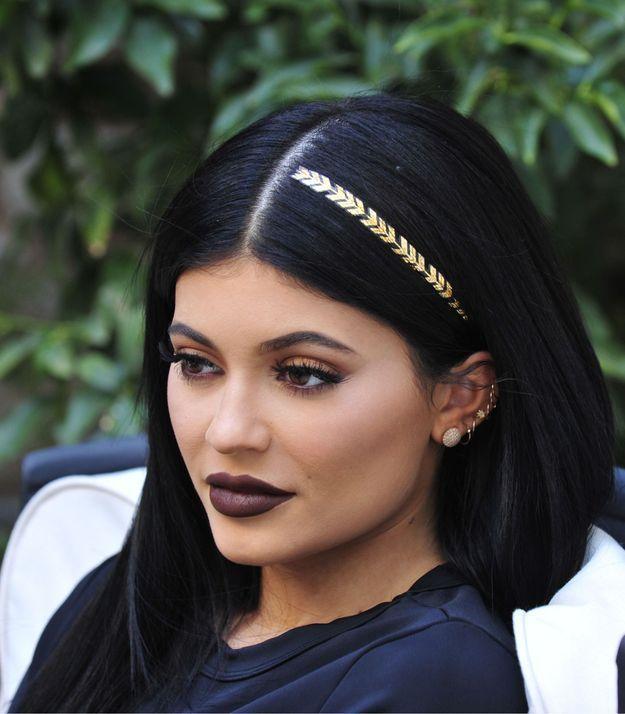 Kylie Jenner et ses cheveux foncés surmontés d'un tatouage doré
