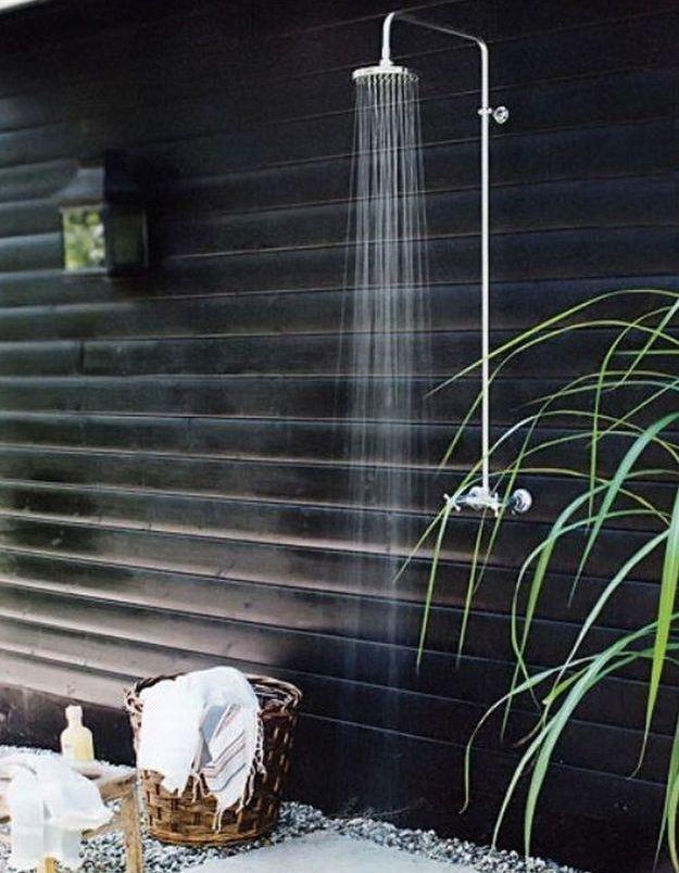 Une douche extérieure devant un mur noir