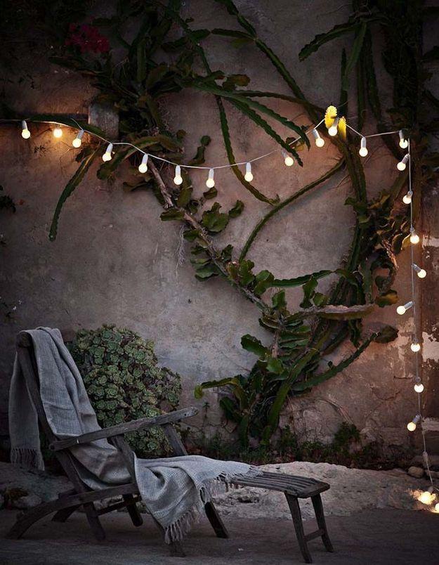 Coin sieste dans le jardin accessoirisé d'une guirlande lumineuse pour un effet cosy