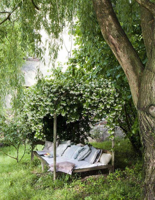 Coin sieste dans le jardin sous une pergola végétale