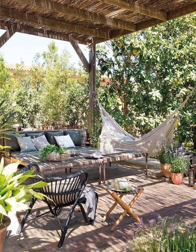 Coin sieste dans le jardin via un hamac installé sous une pergola