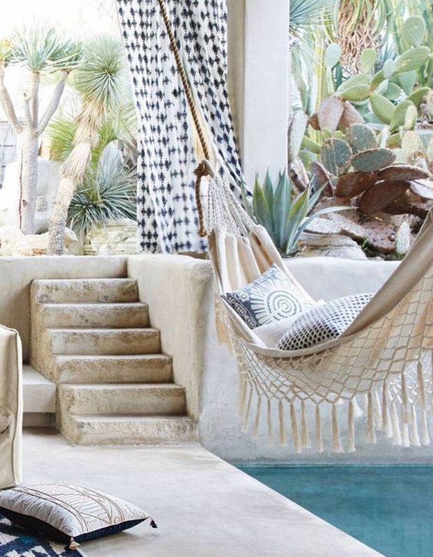 Coin sieste dans le jardin via un hamac suspendu entre la terrasse et la piscine