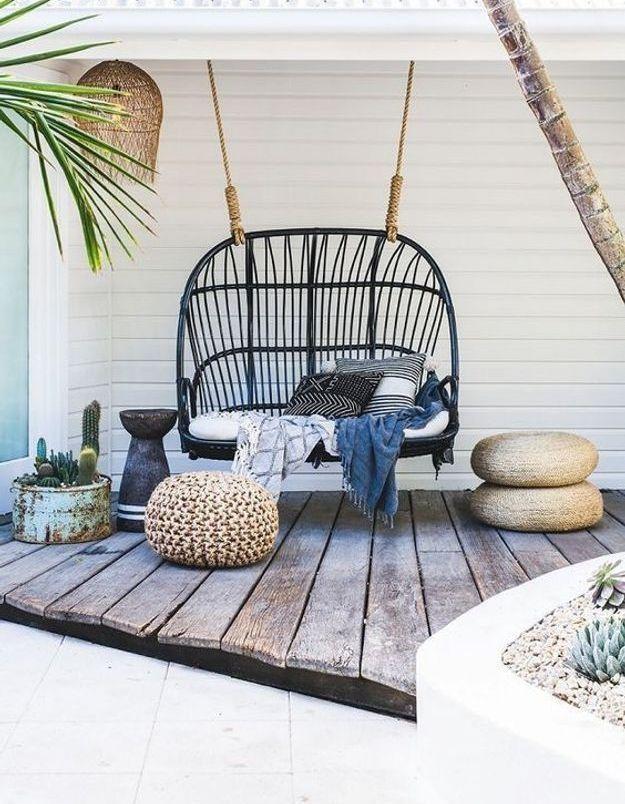 Coin sieste dans le jardin via une balancelle en rotin installée à l'abri des regards