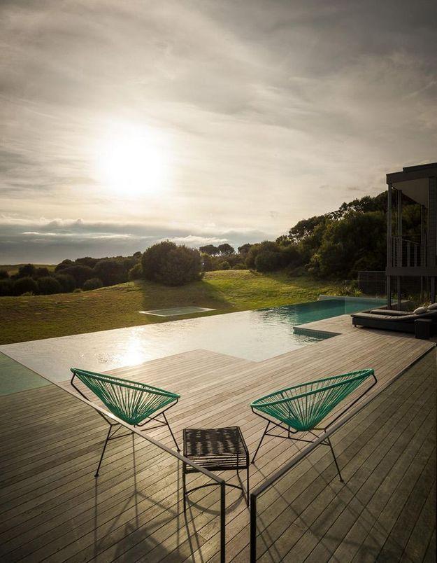 Un fauteuil Acapulco bleu autour de la piscine
