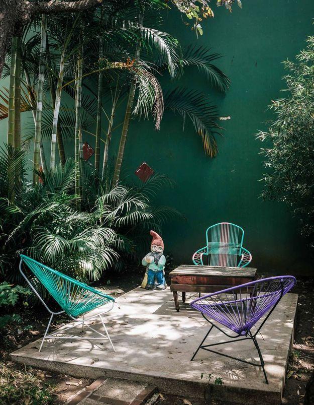 Un fauteuil Acapulco coloré dans un jardin exotique