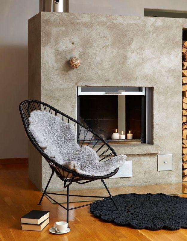 Un fauteuil Acapulco noir près d'une cheminée en béton
