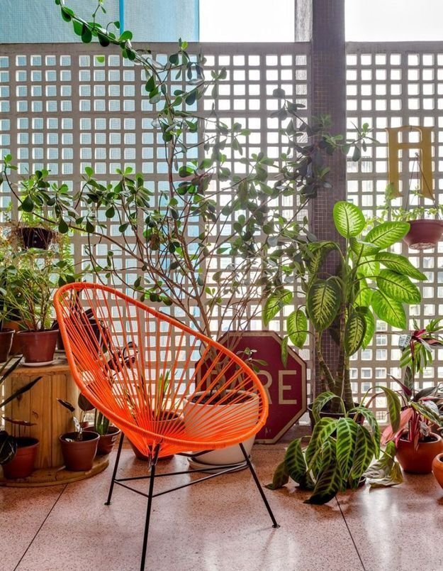Un fauteuil Acapulco orange sur un balcon citadin
