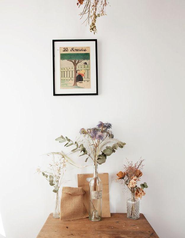 Des bouquets de fleurs séchées dans des bouteilles