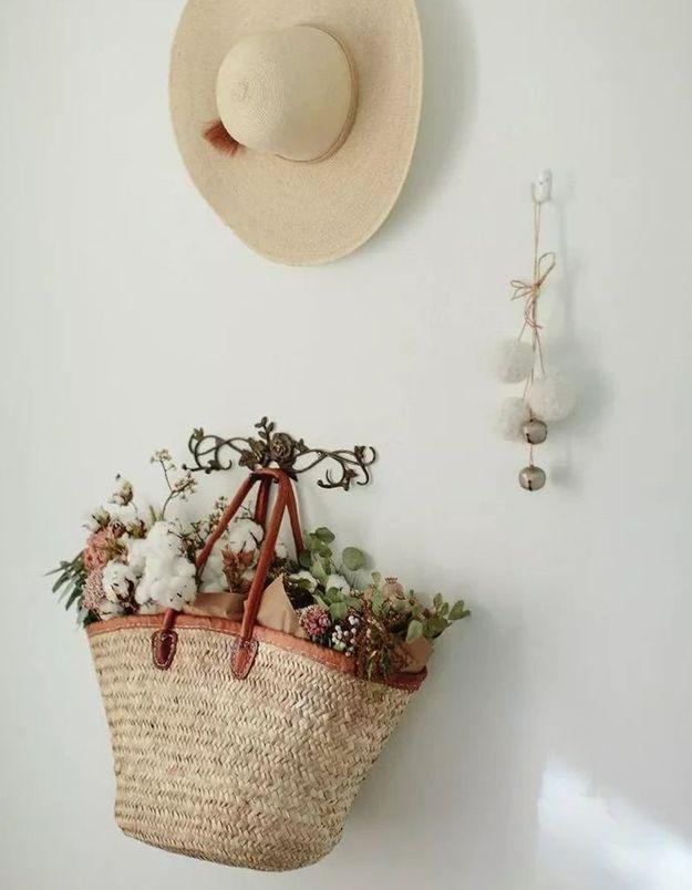 Des fleurs séchées dans un panier suspendu à une patère