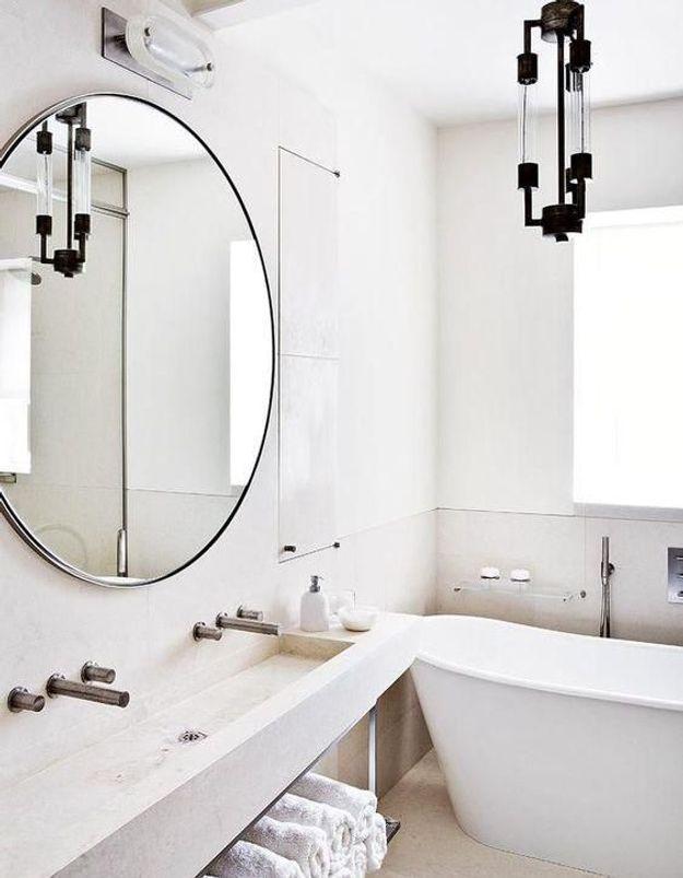 Le miroir rond dans une salle de bains blanche pour booster la déco