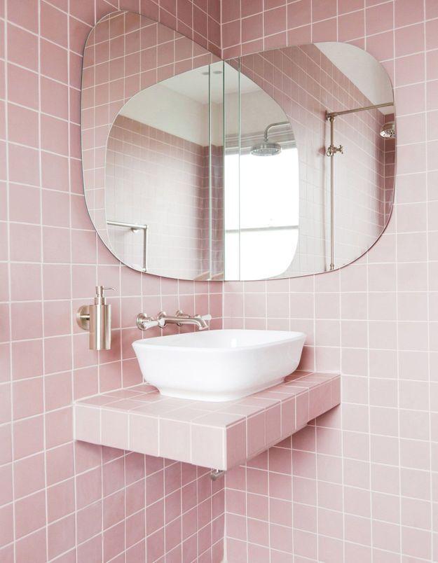 Une salle de bains rose entièrement carrelée