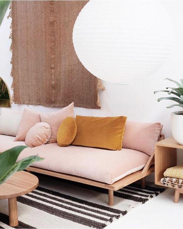 Un canapé rose associé à des coussins couleur moutarde