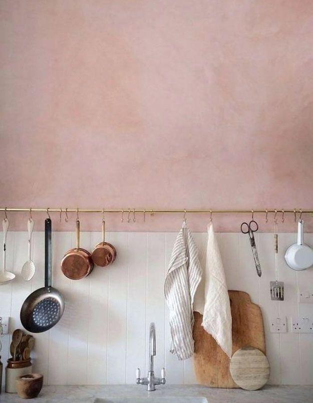 Un mur de cuisine rose accessoirisé d'une barre de crédence dorée