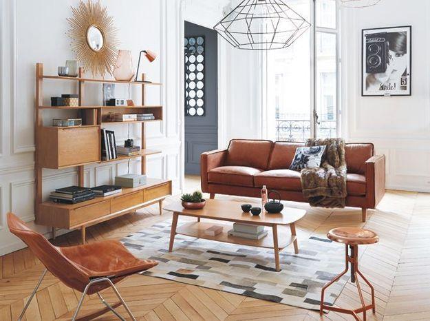 Un parquet en chevrons associé à du mobilier rétro en bois pour un salon vintage