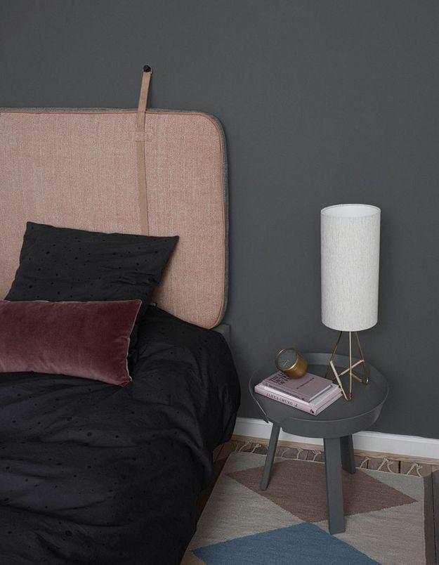 Une chambre grise au linge de lit foncé