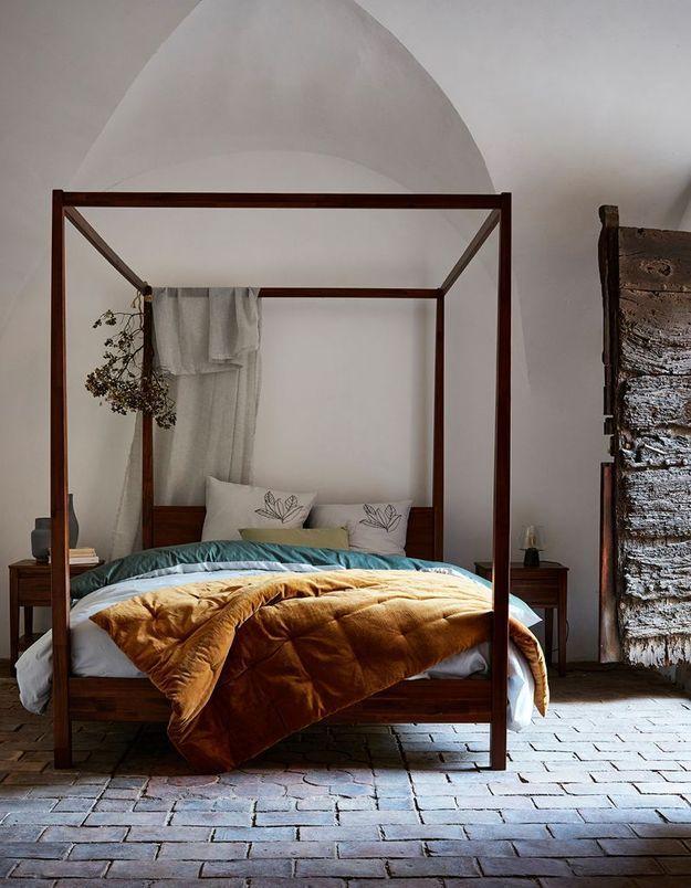 Suspendez des fleurs séchées au lit à baldaquin de la chambre