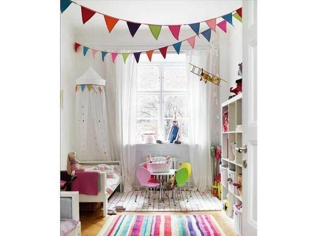Des fanions multicolores au plafond pour égayer les murs blancs