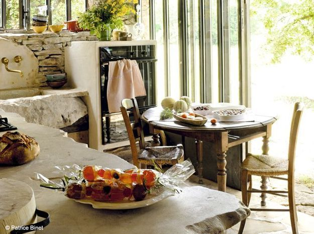 Une cuisine campagne avec plan de travail en pierre