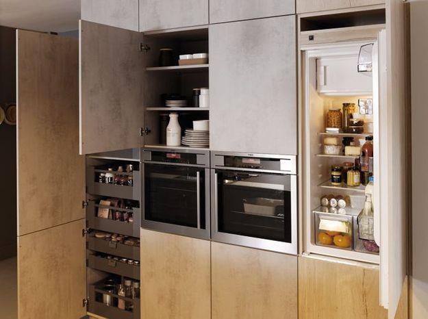 Un réfrigérateur encastré dans un placard en bois