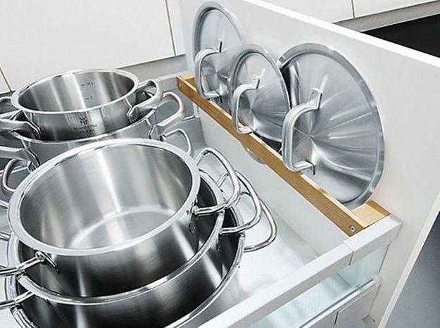 Des placards de cuisine pratiques qui accueillent des supports pour couvercles