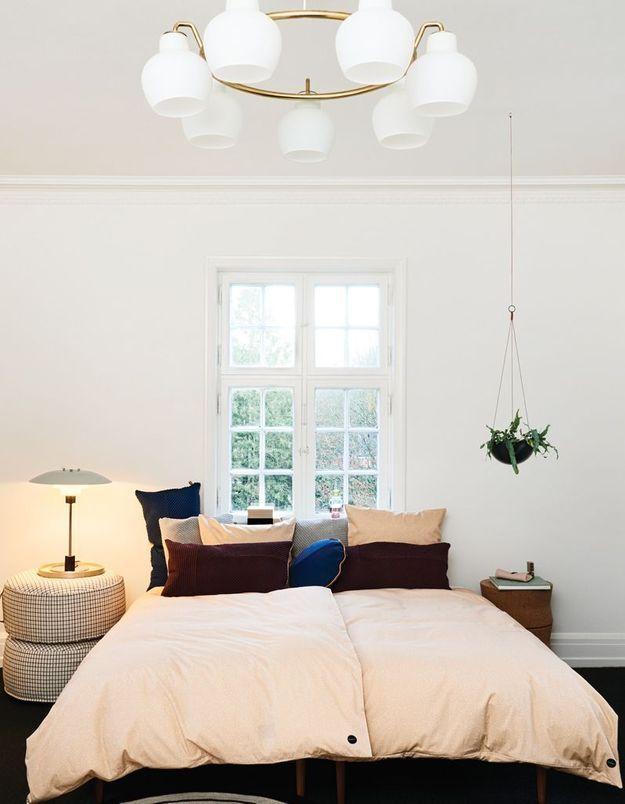 Une fenêtre en tête de lit pour une petite chambre plus profonde