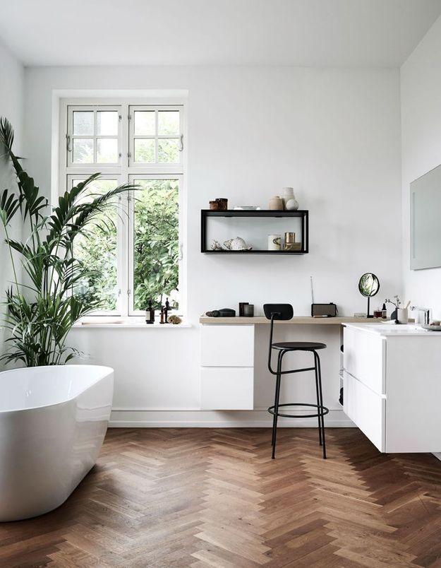 Une salle de bains blanche réchauffée par un parquet en chevrons