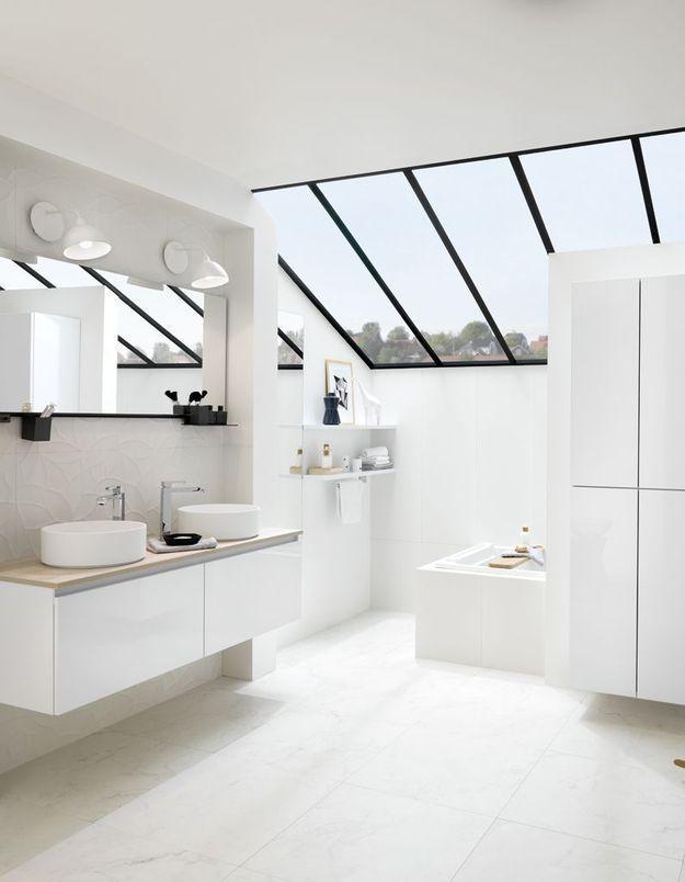 Une salle de bains blanche rehaussée d'une verrière noire