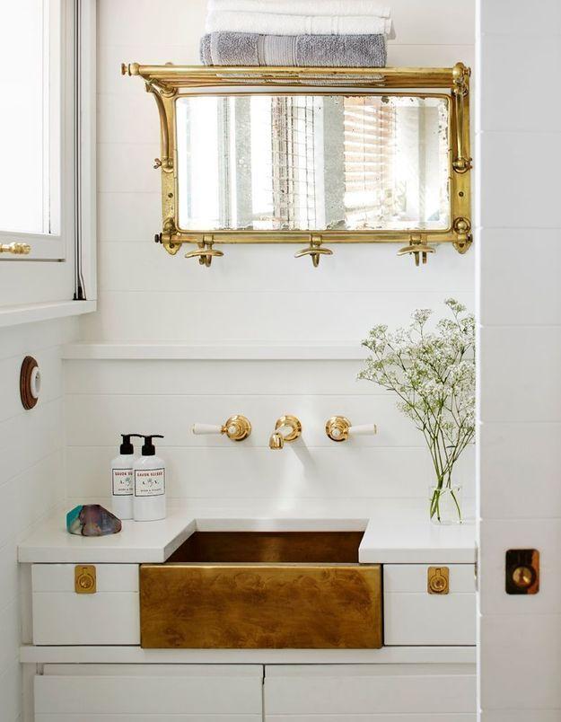 Une salle de bains blanche rendue chic grâce à des touches dorées