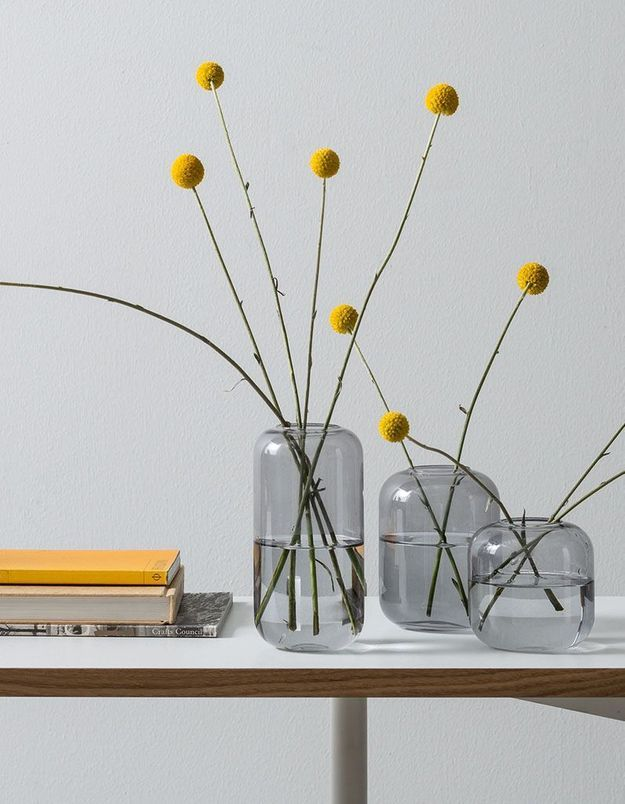 Des bouquets printaniers minimalistes via du craspédia dans un trio de vases identiques