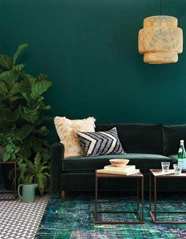 Mur, plantes mobilier et textiles cohabitent dans un salon vert