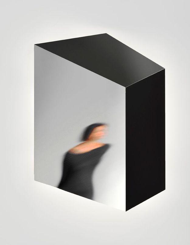Un canapé gris accompagné d'un miroir contemporain