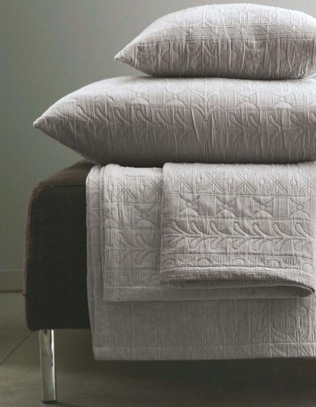 Une canapé gris accompagné d'un plaid au coloris délicat