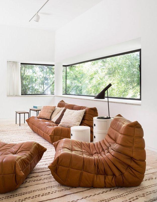 Le canapé, la lisseuse et le pouf Togo en cuir camel dans un salon lumineux